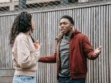 multiethnic couple scolding on street